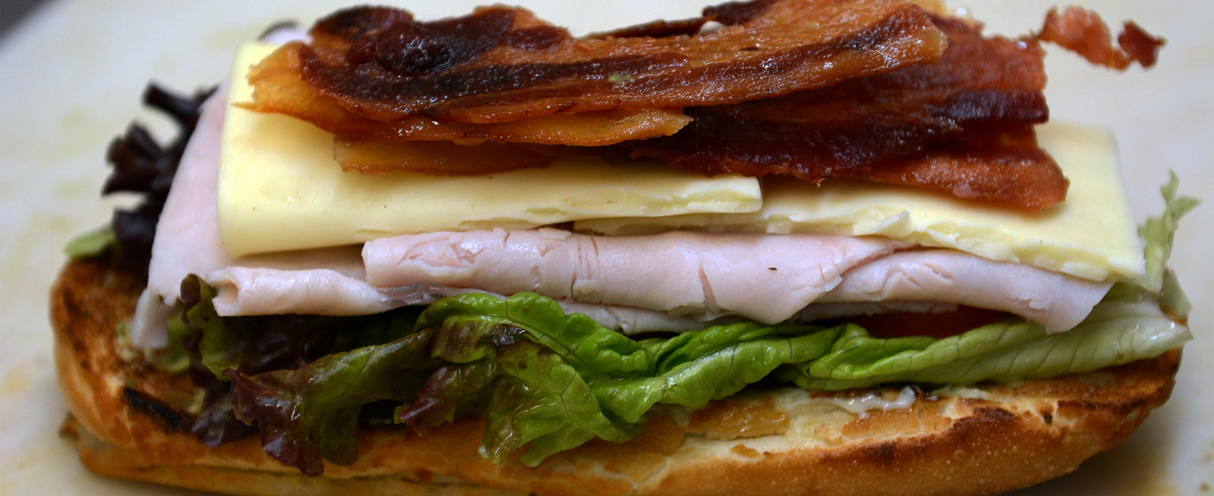 A sandwich with bacon, cheese, turkey, lettuce and tomato plus mayonnaise and spices is just fantastic!